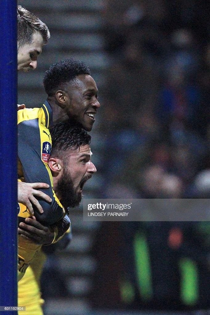 Arsenal's French striker Olivier Giroud (bottom) celebrates with Arsenal's English striker Danny Welbeck and Arsenal's Welsh midfielder Aaron Ramsey (up) after scoring their second goal during the English FA Cup third round football match between Preston North End and Arsenal at Deepdale in north west England on January 7, 2017. Arsenal won the game 2-1. / AFP / Lindsey PARNABY / RESTRICTED TO EDITORIAL USE. No use with unauthorized audio, video, data, fixture lists, club/league logos or 'live' services. Online in-match use limited to 75 images, no video emulation. No use in betting, games or single club/league/player publications. /