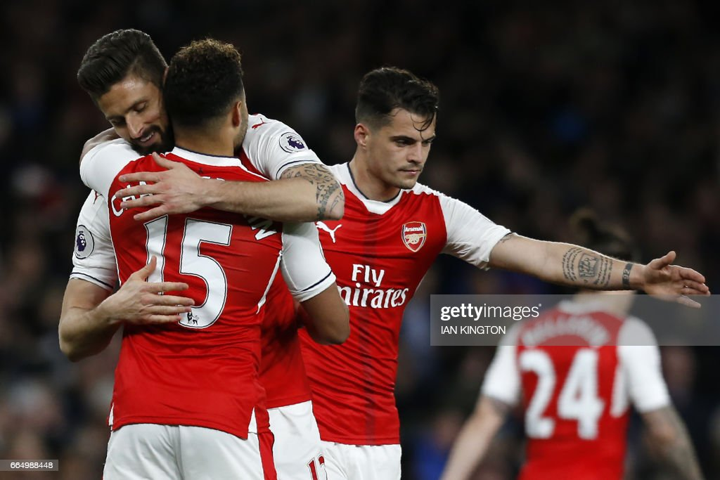 Arsenal's French striker Olivier Giroud (L) celebrates with Arsenal's English midfielder Alex Oxlade-Chamberlain after scoring their third goal during the English Premier League football match between Arsenal and West Ham United at the Emirates Stadium in London on April 5, 2017. Arsenal won the match 3-0. / AFP PHOTO / Ian KINGTON / RESTRICTED TO EDITORIAL USE. No use with unauthorized audio, video, data, fixture lists, club/league logos or 'live' services. Online in-match use limited to 75 images, no video emulation. No use in betting, games or single club/league/player publications. /