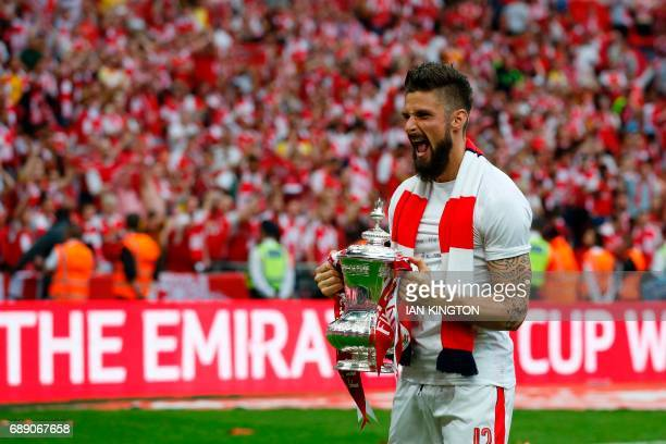 Arsenal's French striker Olivier Giroud celebrates with the FA Cup trophy as Arsenal players celebrate their victory over Chelsea on the pitch after...