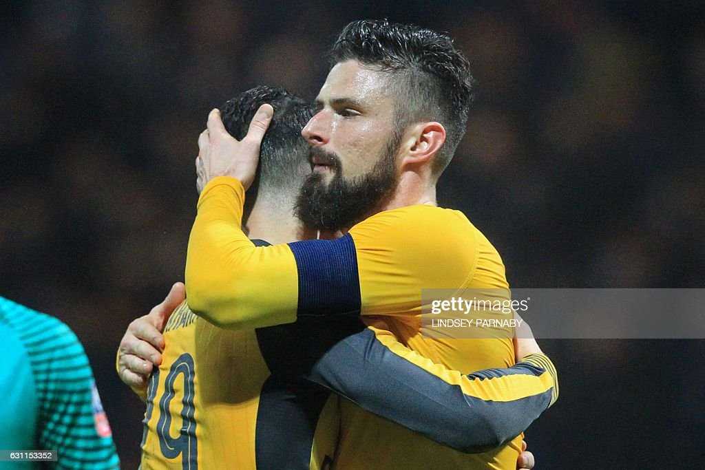 Arsenal's French striker Olivier Giroud (R) embraces Arsenal's Swiss midfielder Granit Xhaka on the pitch after the English FA Cup third round football match between Preston North End and Arsenal at Deepdale in north west England on January 7, 2017. Arsenal won the game 2-1. / AFP / Lindsey PARNABY / RESTRICTED TO EDITORIAL USE. No use with unauthorized audio, video, data, fixture lists, club/league logos or 'live' services. Online in-match use limited to 75 images, no video emulation. No use in betting, games or single club/league/player publications. /