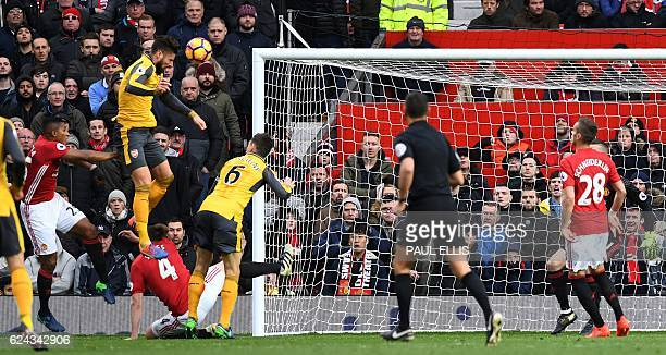 Arsenal's French striker Olivier Giroud jumps to score his team's first goal during the English Premier League football match between Manchester...