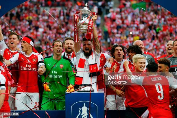 Arsenal's French striker Olivier Giroud lifts the FA Cup trophy as Arsenal players celebrate their win over Chelsea on the pitch after the English FA...