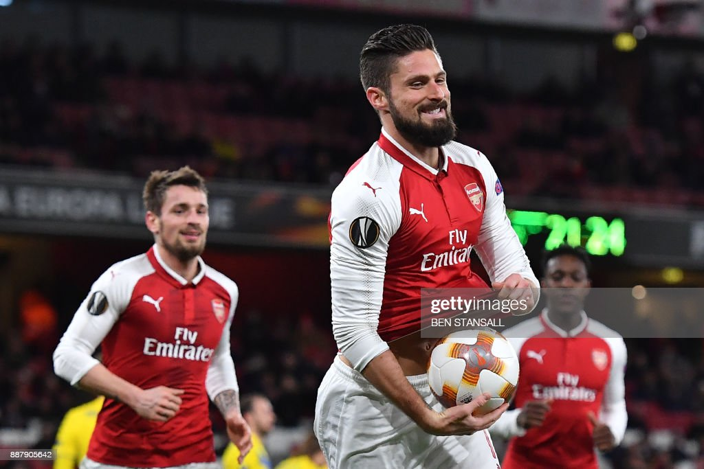 TOPSHOT - Arsenal's French striker Olivier Giroud pops a ball up his shirt as he celebrates scoring a penalty, the fifth goal, during the Europa League Group H stage football match between Arsenal and Bate Borisov at the Emirates Stadium in London on December 7, 2017. / AFP PHOTO / Ben STANSALL / RESTRICTED TO EDITORIAL USE. No use with unauthorized audio, video, data, fixture lists, club/league logos or 'live' services. Online in-match use limited to 75 images, no video emulation. No use in betting, games or single club/league/player publications. /
