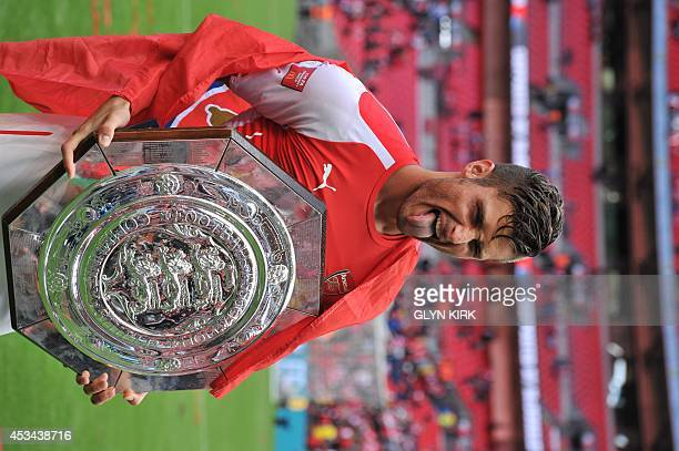 Arsenal's French striker Olivier Giroud poses with the Community Shield trophy after Arsenal won the FA Community Shield football match between...