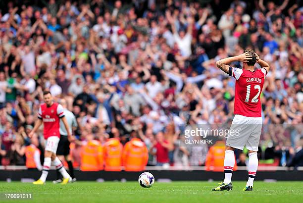 Arsenal's French striker Olivier Giroud reacts after Aston Villa's Spanish defender Antonio Luna scores Villa's third goal during the English Premier...