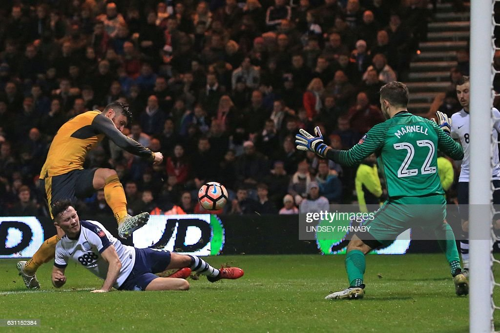 Arsenal's French striker Olivier Giroud (L) shoots to score the second goal past Preston's Welsh goalkeeper Chris Maxwell during the English FA Cup third round football match between Preston North End and Arsenal at Deepdale in north west England on January 7, 2017. Arsenal won the game 2-1. / AFP / Lindsey PARNABY / RESTRICTED TO EDITORIAL USE. No use with unauthorized audio, video, data, fixture lists, club/league logos or 'live' services. Online in-match use limited to 75 images, no video emulation. No use in betting, games or single club/league/player publications. /