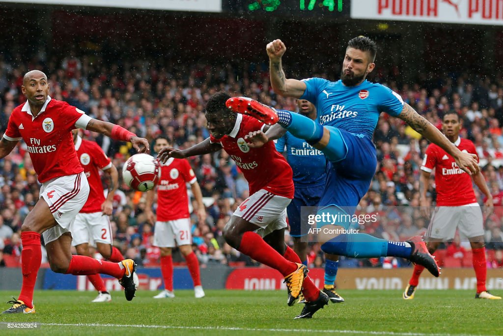 TOPSHOT - Arsenal's French striker Olivier Giroud (R) shoots to score their fouth goal during the pre-season friendly football match between Arsenal and Benfica at The Emirates Stadium in north London on July 29, 2017, the game is one of four matches played over two days for the Emirates Cup. / AFP PHOTO / Ian KINGTON / RESTRICTED TO EDITORIAL USE. No use with unauthorized audio, video, data, fixture lists, club/league logos or 'live' services. Online in-match use limited to 75 images, no video emulation. No use in betting, games or single club/league/player publications. /