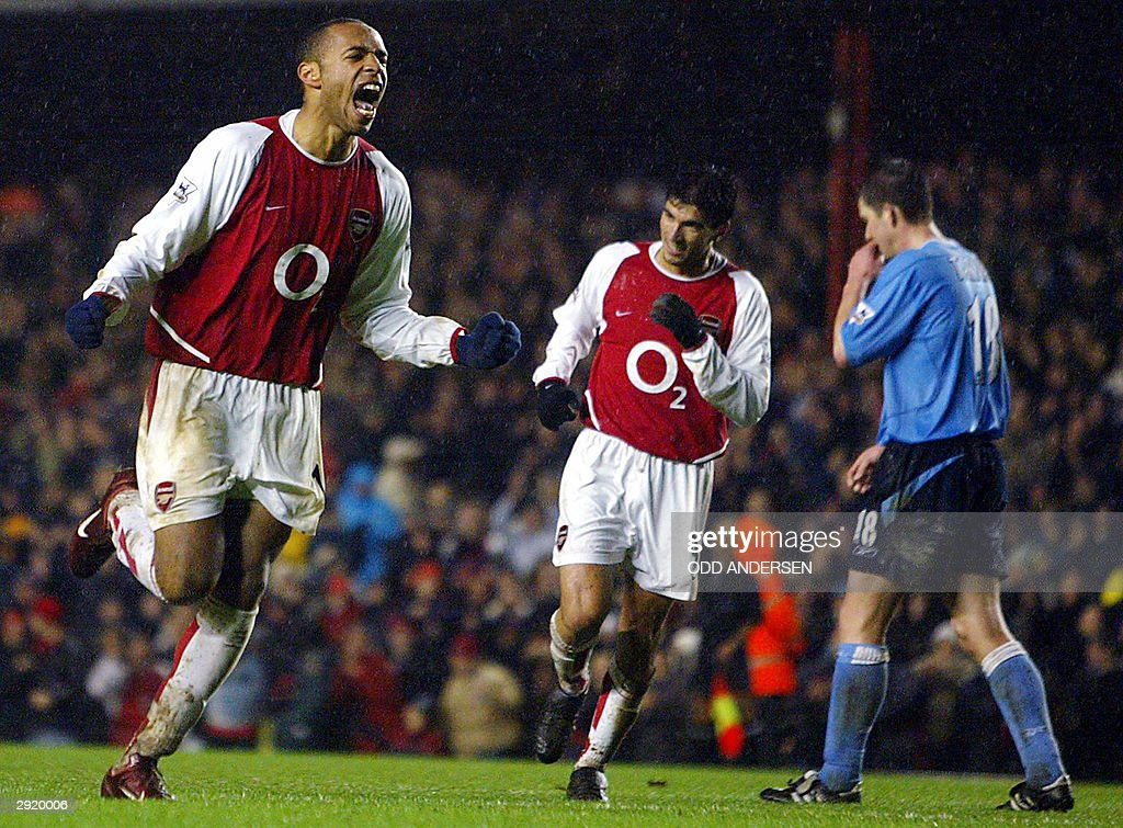 Arsenal's French striker Thierry Henry (L) celebrates his goal with teammate Jose Reyes (C) as Michael Tarnatt of Manchester City despairs during their FA Premier League clash at Highbury in London 01 February 2004. Arsenal defeated Manchester City 2-1.