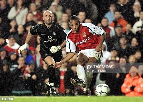 Arsenal's French striker Thierry Henry rounds Manchester United's French goalkeeper Fabien Barthez to slot home Arsenal's third goal during the...