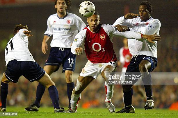 Arsenal's French striker Thierry Henry tries to take the ball through the Middlesbrough defence Luke Wilkshire Jonathan Greening and Ugo Ehiogu...
