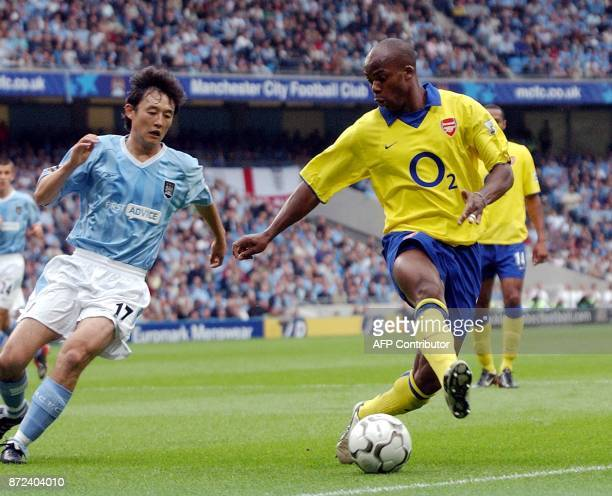 Arsenal's French Sylvain Wiltord vies with Manchester City's Jihai Sun during their Premiership clash at Manchester Stadium in Manchester 31 August...