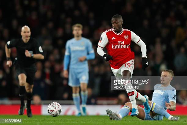 Arsenal's Frenchborn Ivorian midfielder Nicolas Pepe evades a challenge from Leeds United's English midfielder Kalvin Phillips during the English FA...