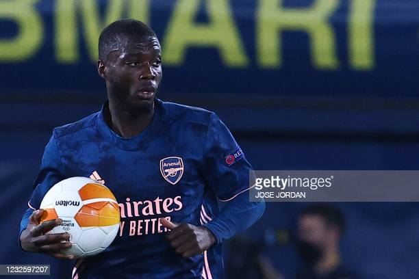 Arsenal's French-born Ivorian midfielder Nicolas Pepe grabs the ball after scoring during the Europa League semi-final first leg football match...