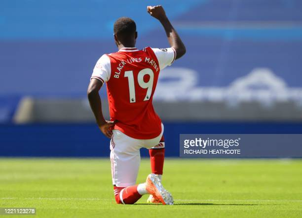 Arsenal's French-born Ivorian midfielder Nicolas Pepe kneels before the English Premier League football match between Brighton and Hove Albion and...