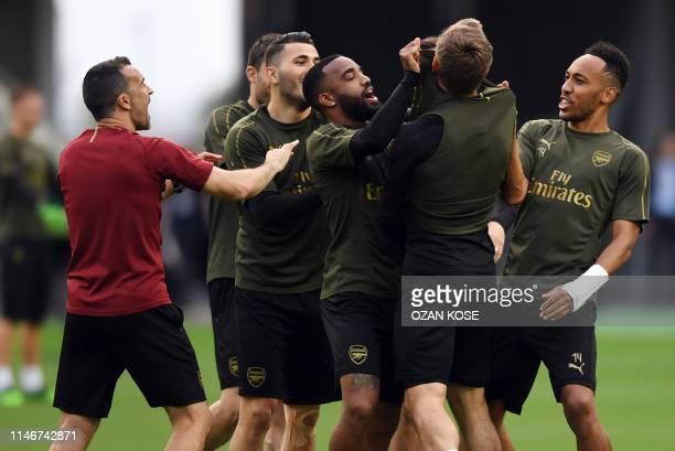 Arsenal's Gabonese striker PierreEmerick Aubameyang and Arsenal's French striker Alexandre Lacazette joke with teammates during a training session at...