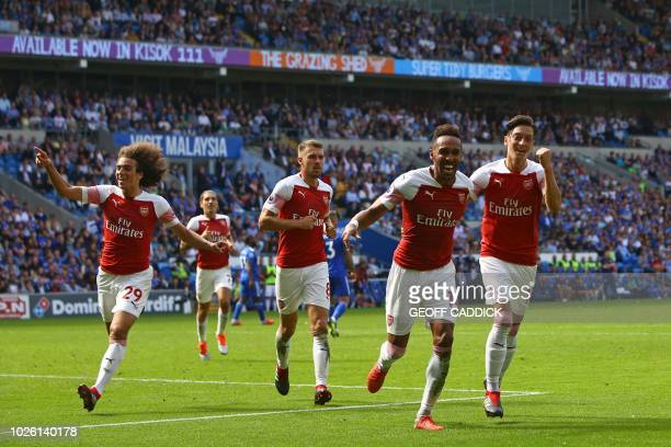 Arsenal's Gabonese striker PierreEmerick Aubameyang celebrates with teammates after scoring their second goal during the English Premier League...