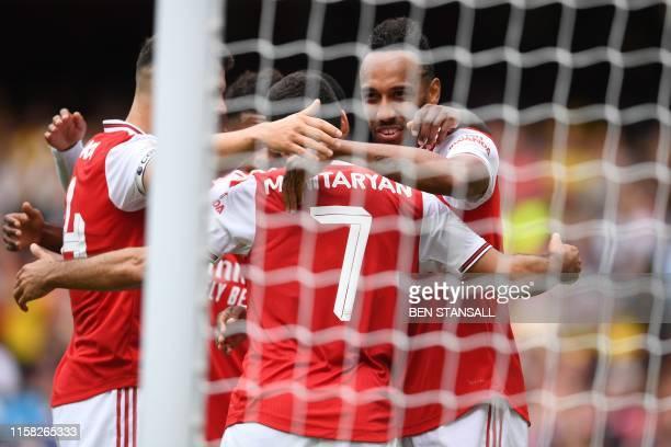 Arsenal's Gabonese striker PierreEmerick Aubameyang celebrates with teammates after scoring the opening goal of the preseason friendly football match...