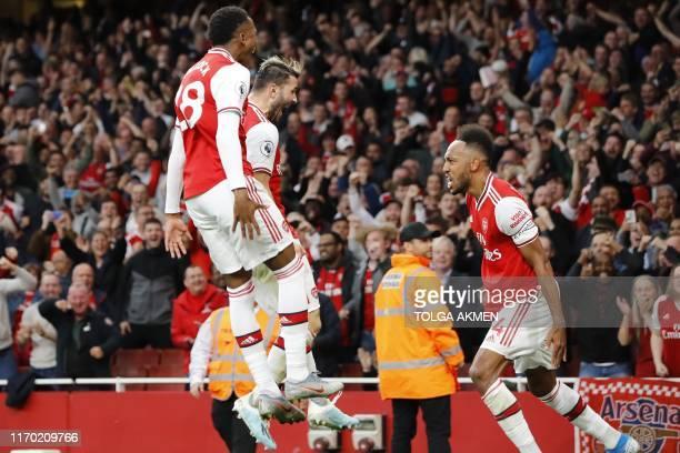 Arsenal's Gabonese striker PierreEmerick Aubameyang celebrates with teammates after scoring their third goal during the English Premier League...