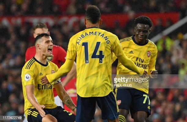 Arsenal's Gabonese striker PierreEmerick Aubameyang celebrates with Arsenal's Swiss midfielder Granit Xhaka and Arsenal's English striker Bukayo Saka...