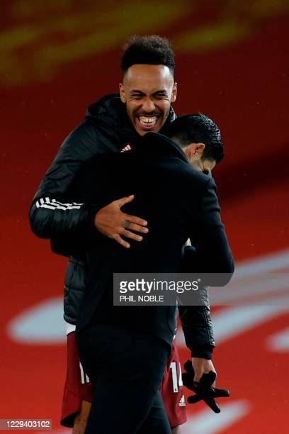 Arsenal's Gabonese striker Pierre-Emerick Aubameyang embraces Arsenal's Spanish manager Mikel Arteta at the end of the English Premier League...