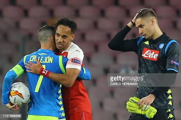 Arsenal's Gabonese striker PierreEmerick Aubameyang embraces Napoli's Spanish forward Jose Callejon as Napoli's Italian goalkeeper Alex Meret walks...