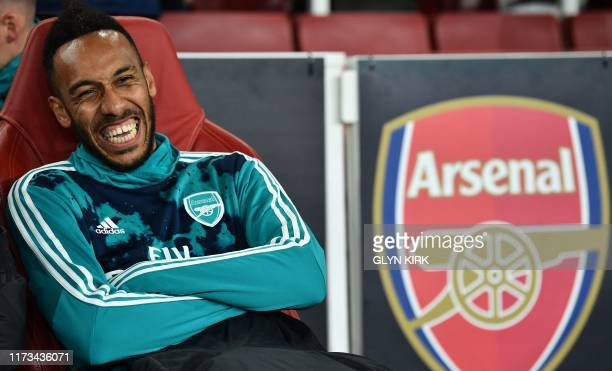 Arsenal's Gabonese striker PierreEmerick Aubameyang laughs on the substitute's bench ahead of the UEFA Europa League Group F football match between...