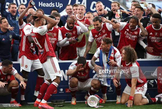 TOPSHOT Arsenal's Gabonese striker PierreEmerick Aubameyang reacts after dropping the winner's trophy as the team celebrates victory after the...
