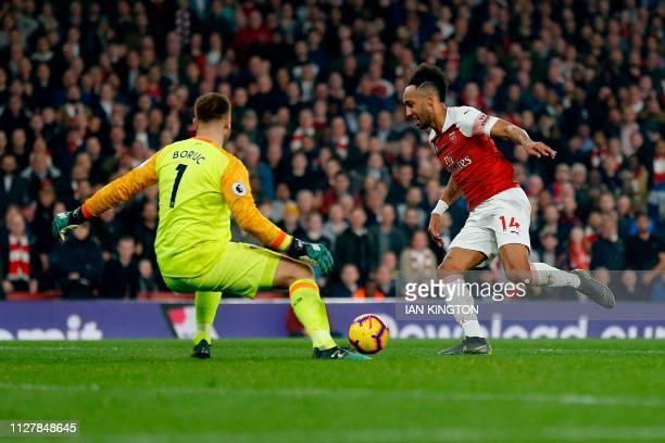 Arsenal's Gabonese striker PierreEmerick Aubameyang runs around Bournemouth's Polish goalkeeper Artur Boruc to scores his team's fourth goal during...