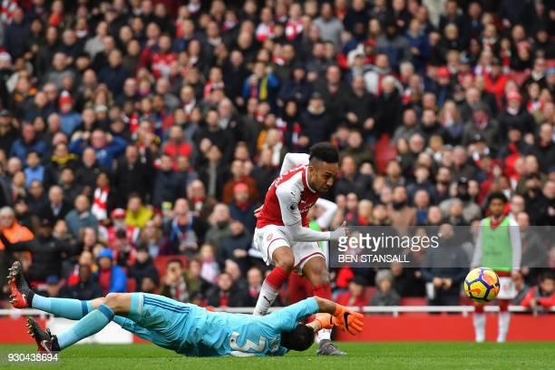 Arsenal's Gabonese striker PierreEmerick Aubameyang scores Arsenal's second goal past the outstretched arms of Watford's Greek goalkeeper Orestis...