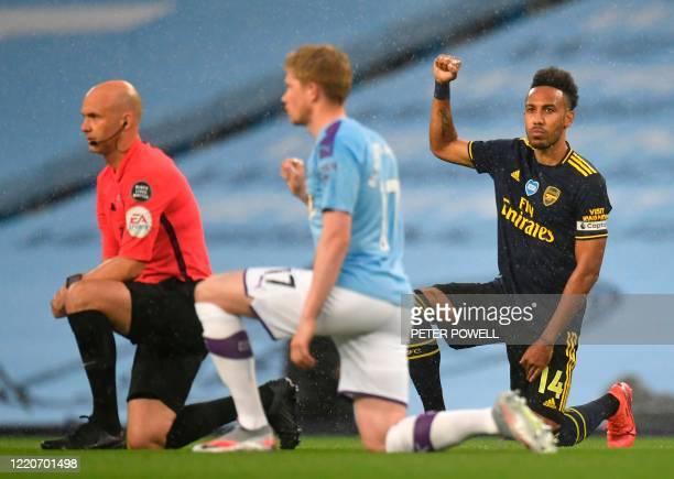 TOPSHOT Arsenal's Gabonese striker PierreEmerick Aubameyang takes a knee alongside Manchester City's Belgian midfielder Kevin De Bruyne and Referee...