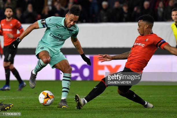 Arsenal's Gabonese striker PierreEmerick Aubameyang vies with Rennes' Mozambican defender Mexer during the UEFA Europa League round of 16 first leg...