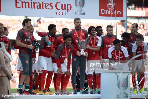 Arsenal's German captain Per Mertesacker holds the Emirates Cup trophy as the team celebrates at the close of the preseason friendly football match...