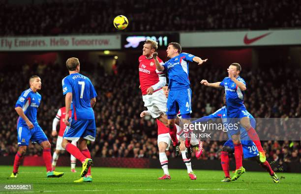 Arsenal's German defender Per Mertesacker contests a high ball with Hull City's Northern Irish defender Alex Bruce during the English Premier League...