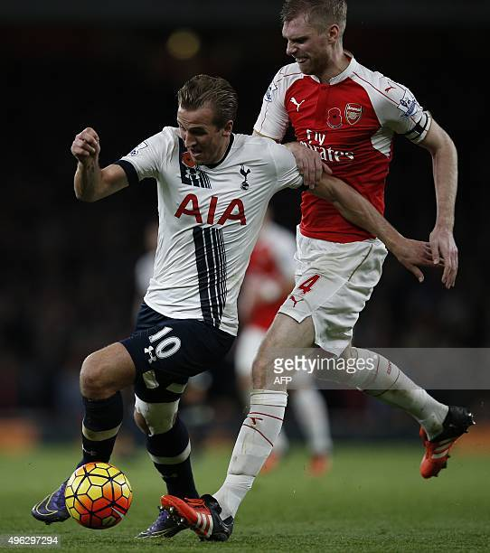 Arsenal's German defender Per Mertesacker follows Tottenham Hotspur's English striker Harry Kane during the English Premier League football match...