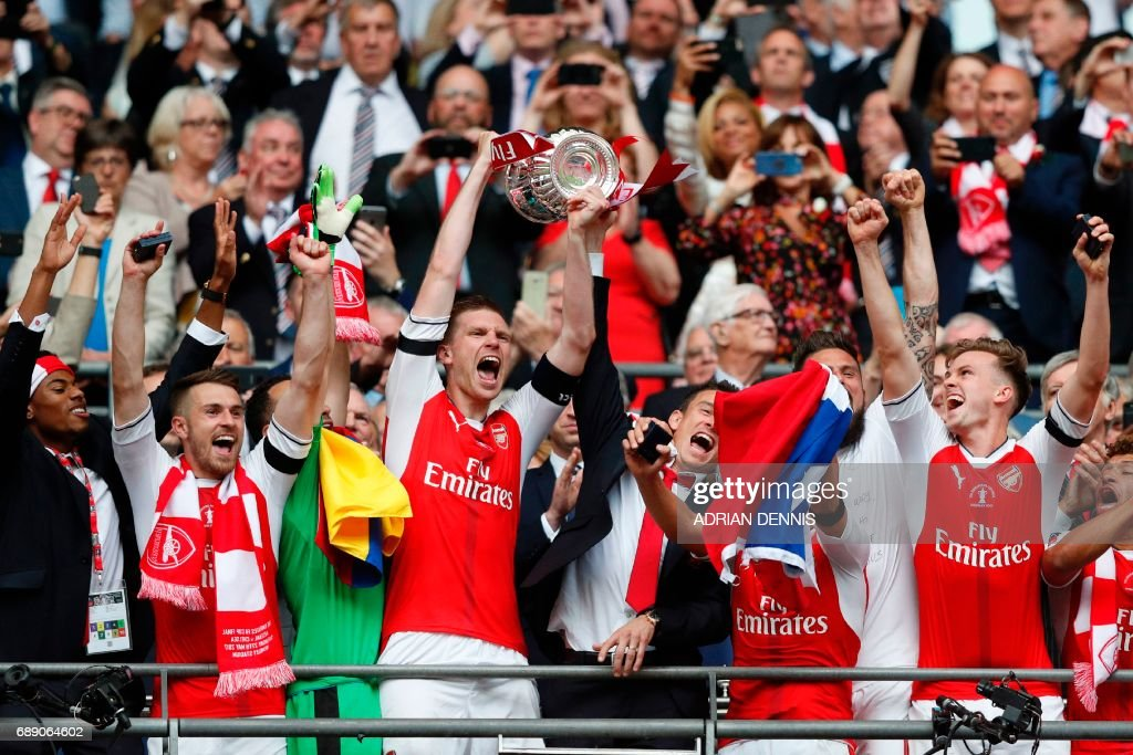 Arsenal's German defender Per Mertesacker lifts the FA Cup trophy as Arsenal players celebrate their victory over Chelsea in the English FA Cup final football match between Arsenal and Chelsea at Wembley stadium in London on May 27, 2017. Aaron Ramsey scored a 79th-minute header to earn Arsenal a stunning 2-1 win over Double-chasing Chelsea on Saturday and deliver embattled manager Arsene Wenger a record seventh FA Cup. / AFP PHOTO / Adrian DENNIS / NOT