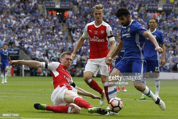 Arsenal's German defender Per Mertesacker slides in to tackle Chelsea's Brazilianborn Spanish striker Diego Costa during the English FA Cup final...