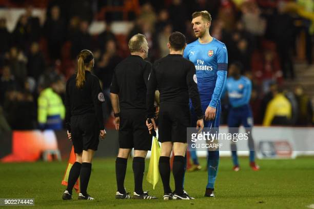 Arsenal's German defender Per Mertesacker speaks to the referee Jonathan Moss after the English FA Cup third round football match between Nottingham...