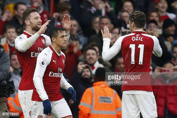 Arsenal's German defender Shkodran Mustafi celebrates scoring the team's first goal with Arsenal's Chilean striker Alexis Sanchez and Arsenal's...