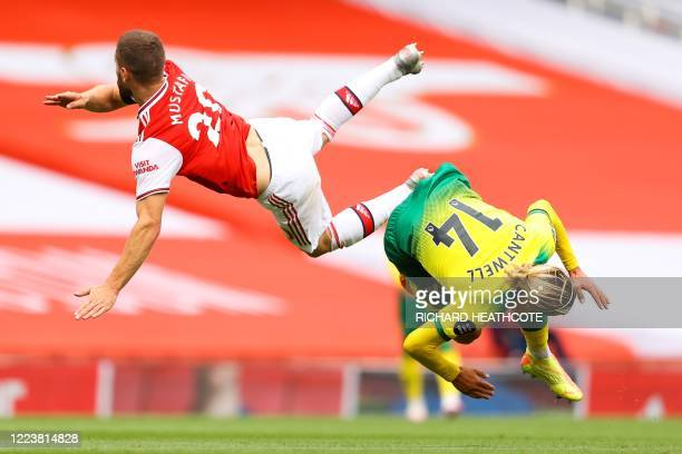 Arsenal's German defender Shkodran Mustafi fights for the ball with Norwich City's English midfielder Todd Cantwell during the English Premier League...