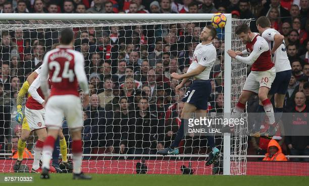 Arsenal's German defender Shkodran Mustafi heads the ball to score the opening goal during the English Premier League football match between Arsenal...