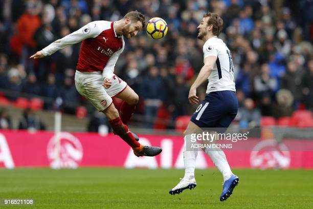 Arsenal's German defender Shkodran Mustafi heads the ball under pressure from Tottenham Hotspur's English striker Harry Kane during the English...