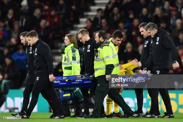 Arsenal's German defender Shkodran Mustafi is taken from the pitch on a stretcher after picking up an injury during the English FA Cup fourth round...
