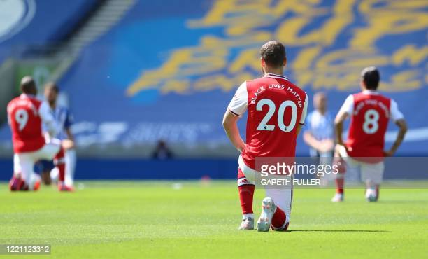 TOPSHOT Arsenal's German defender Shkodran Mustafi takes a knee to show support for the Black Lives Matter movement and as a protest against racism...