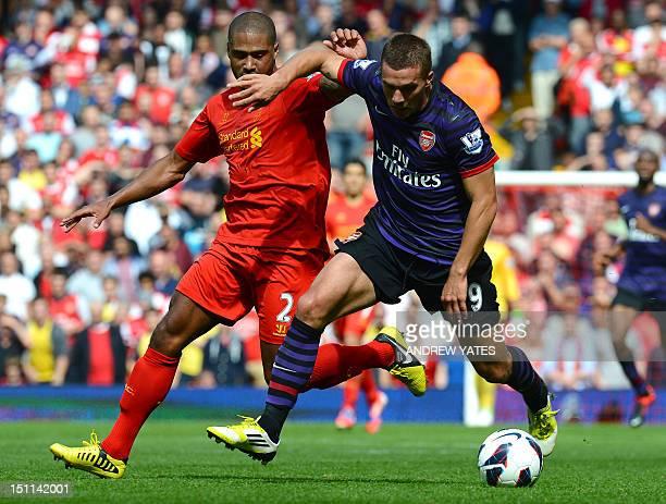 Arsenal's German forward Lukas Podolski vies with Liverpool's English defender Glen Johnson during the English Premier League football match between...