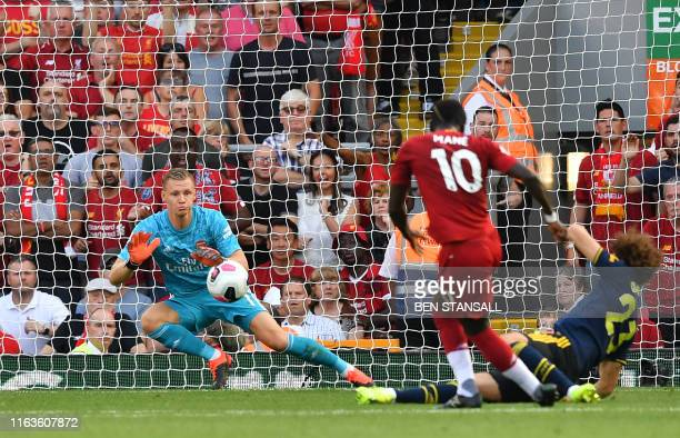 Arsenal's German goalkeeper Bernd Leno dives to save a shot from Liverpool's Senegalese striker Sadio Mane during the English Premier League football...