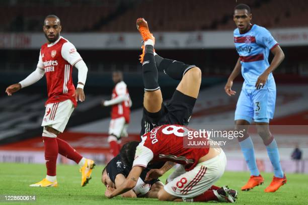Arsenal's German goalkeeper Bernd Leno goes over the back of Arsenal's Spanish midfielder Dani Ceballos as he claims the ball during the English...