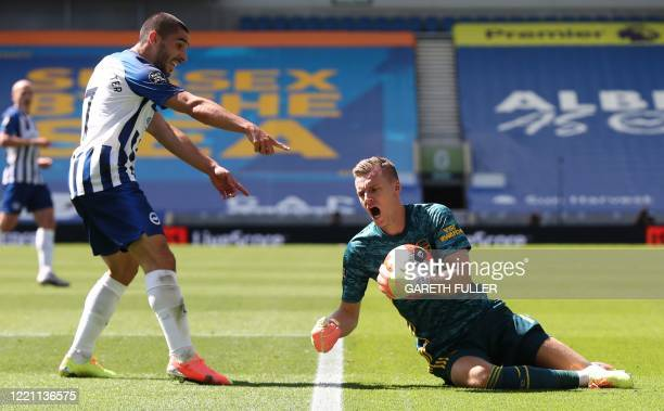 Arsenal's German goalkeeper Bernd Leno is challenged by Brighton's French striker Neal Maupay during the English Premier League football match...