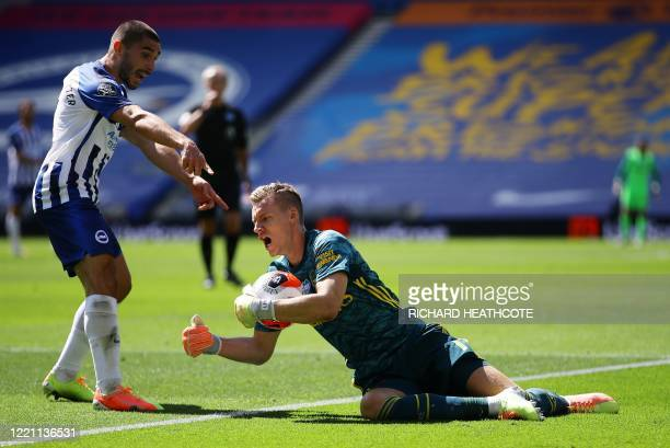 Arsenal's German goalkeeper Bernd Leno is injured as he collects the ball against Brighton's French striker Neal Maupay during the English Premier...