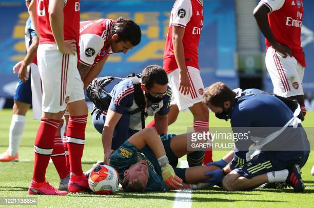 Arsenal's German goalkeeper Bernd Leno is treated by medical staff during the English Premier League football match between Brighton and Hove Albion...