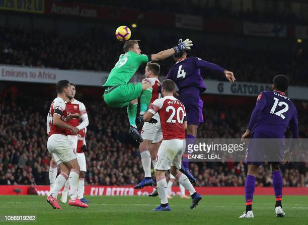 Arsenal's German goalkeeper Bernd Leno jumps but misses the ball as Liverpool's Dutch defender Virgil van Dijk has an attempt on goal during the...